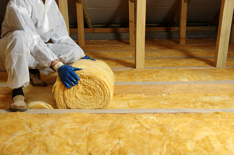 house attic insulation - construction worker installing glass wool