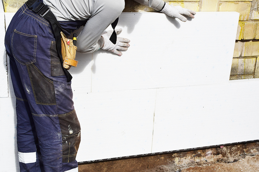 worker installing white rigid polyurethane foam sheet on building wall facade for energy saving. diy, house improvement and insulation concept.