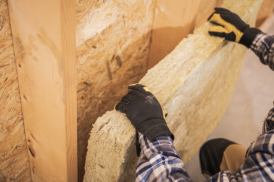 synthetic mineral fibers wall insulation job. construction worker insulating house walls with thermal material.